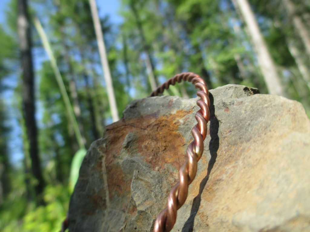 Copper Energy Ring, as sold by Woven Cosmos displayed on a rock in a spring forest.